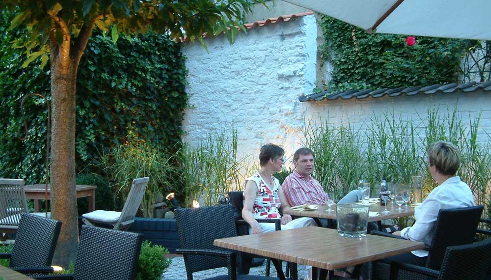 Gasten aan een tafeltje in de tuin van een restaurant bij avond